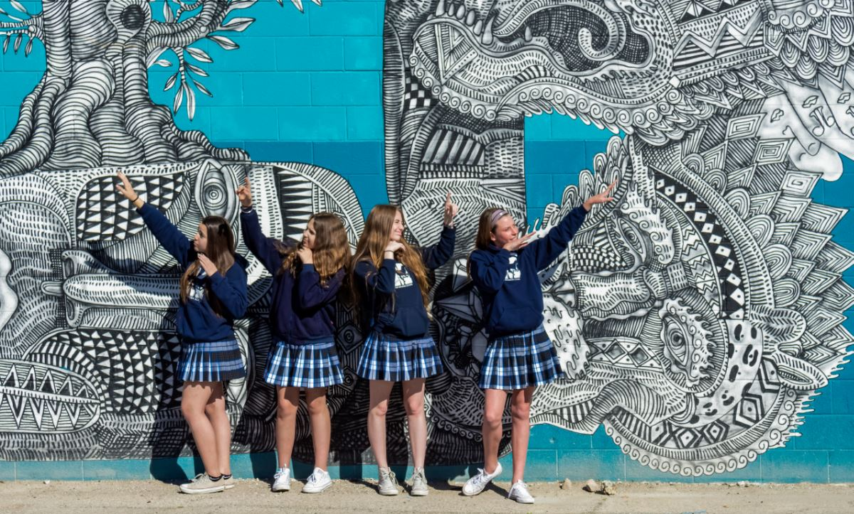 students posting in front of wall art mural